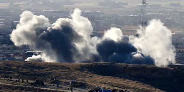 Smoke billows from the northern Iraqi town of Sinjar during an operation by Iraqi Kurdish forces backed by US-led strikes on November 12, 2015, to retake the town from the Islamic State group and cut a key supply line to Syria. The autonomous Kurdish region's security council said up to 7,500 Kurdish fighters would take part in the operation, which aims to retake Sinjar 'and establish a significant buffer zone to protect the (town) and its inhabitants from incoming artillery.' AFP PHOTO / SAFIN HAMED        (Photo credit should read SAFIN HAMED/AFP/Getty Images)