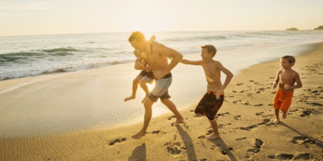 USA, California, Laguna Beach, Father playing football on beach with his three sons (6-7, 10-11, 14-15)