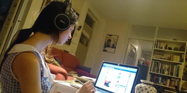 Girl with headphone checks her social media on her laptop