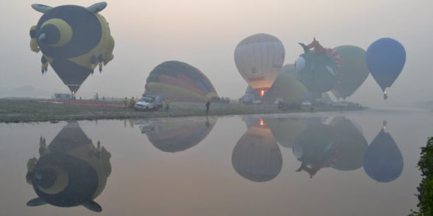 Hot air balloons are reflected on the water of the Yamuna River on a misty morning on the second day of the Taj Balloon festival in Agra, India, Sunday, Nov.15, 2015. The three-day event ends Monday. (AP Photo/Pawan Sharma)