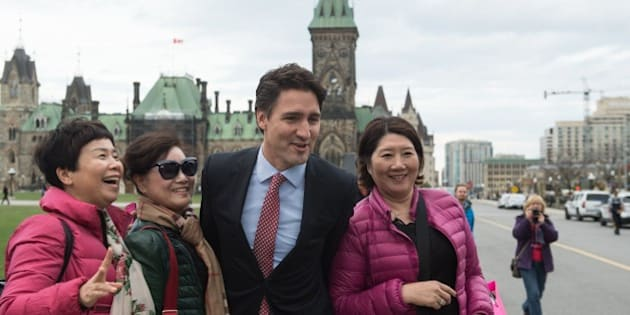 Canadian Liberal Party leader Justin Trudeau poses for a selfie with tourists as he walks from the parliament to give a press conference in Ottawa on October 20, 2015 after winning the general elections.    AFP PHOTO/NICHOLAS KAMM        (Photo credit should read NICHOLAS KAMM/AFP/Getty Images)