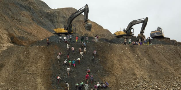In this June 15, 2015 photo, freelance jade miners collect jade stones in an earth dump of a companies' mining field in Hpakant area, Kachin State, Northern Myanmar. Uncontrolled mining of Myanmar's famously valuable jade deposits is enriching individuals and companies tied to the country's former military rulers while exacting a growing human and environmental toll on impoverished Kachin state. (AP Photo/Hkun Lat)