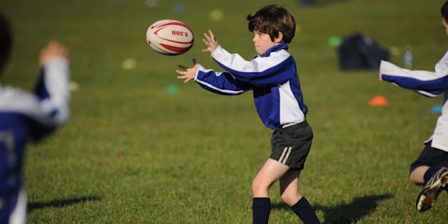 Young boy receiving a pass in a rugby training session on a grass pitch