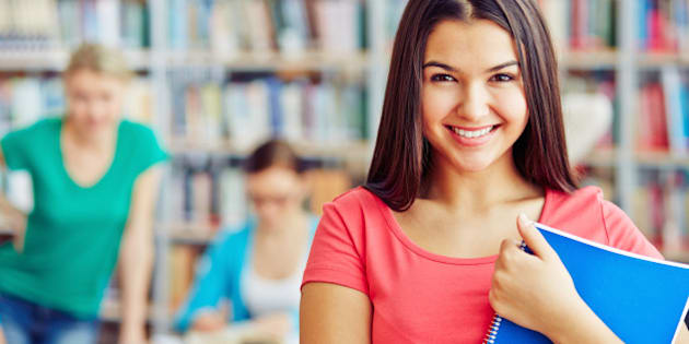 Smiling teenager with copybook looking at camera