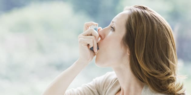 Woman using asthma inhaler