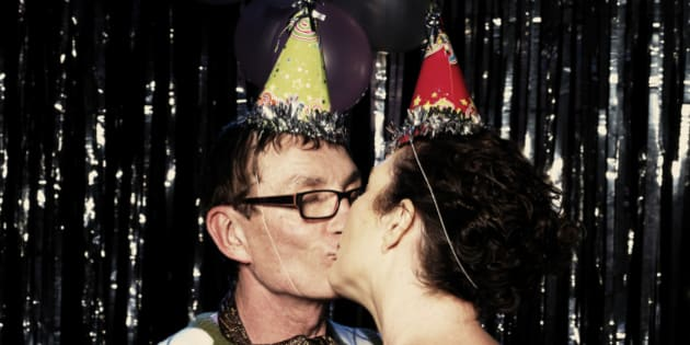 A mature couple kissing at a party