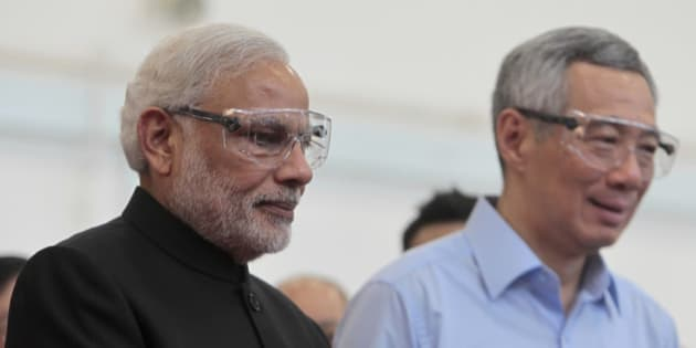 Indian Prime Minister Narendra Modi, left, and Singapore Prime Minister Lee Hsien Loong wear safety goggles before they handle heavy machinery in a workshop at a vocational and technical training institute in Singapore on Tuesday, Nov. 24, 2015. Modi is on a two-day official visit to the city-state. (Wallace Woon/Pool Photo via AP)