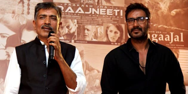 Indian Bollywood actor Ajay Devgn (R) poses for a photograph during a promotional event for new films by Bollywood film producer, director and screenwriter Prakash Jha (L) in Mumbai on October 29, 2014. AFP PHOTO/STR        (Photo credit should read STRDEL/AFP/Getty Images)