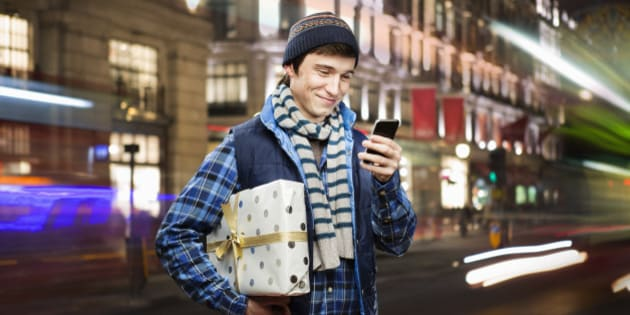 man holding shopping looks at mobilephone in city.
