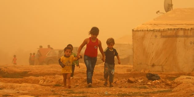 Syrian children walk amid the dust during a sandstorm on September 7, 2015 at a refugee camp on the outskirts of the eastern Lebanese city of Baalbek.   AFP PHOTO / STR        (Photo credit should read -/AFP/Getty Images)
