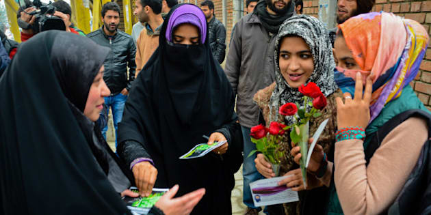 SRINAGAR, KASHMIR- NOVEMBER 12: A group of Muslim girls present red roses to the Muslim girls for wearing Hijab during a campaign on November 12, 2015 in Srinagar, the summer capital of Indian administered Kashmir, India. A Muslim group, the International Muslim Unity Council (IMUC), offered red roses to girl students outside a college to promote the wearing of the hijab (full body veil). A group of girls, associated with the IMUC, stood outside the college and distributed roses, scarves, stoles and religious pamphlets to girl students. The group said the hijab campaign was part of the ongoing campaigns in New Delhi's Jawaharlal Nehru University, Uttar Pradesh's Aligarh Muslim University and Hyderabad University in India. The group is planning to target other educational institutions too and claims that use of the hijab was going down in the Muslim majority region. (Photo by Yawar Nazir/Getty Images)