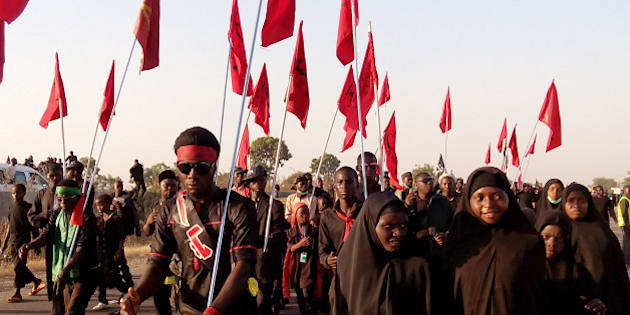 Shiite Muslims march on the highway during a symbolic procession commemorating the 40th anniversary of the Ashura religious ceremony on November 27, 2015 in the village of Dakasoye, northern Nigeria, following a suicide bombing attack. At least 21 people were killed on November 27 when a suicide bomber blew himself up in the crowds at a Shia Muslim procession near the north Nigerian city of Kano, in the latest violence to hit the troubled region. An AFP reporter in Dakasoye said the road was splattered with bloodstains but the followers had continued their march. AFP PHOTO / AMINU ABUBAKAR / AFP / AMINU ABUBAKAR        (Photo credit should read AMINU ABUBAKAR/AFP/Getty Images)