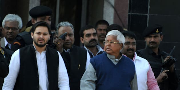 Indian politician Lalu Prasad Yadav (R) walks with his son Tejaswi (L) and security personnel as he leaves Birsa Munda Central Jail in Ranchi on December 16, 2013, following his release from the prison.  Yadav, the head of the Rashtriya Janata Dal (RJD) party has been released some two-and-a-half months after he was convicted in a fodder scam case.     AFP PHOTO/STR        (Photo credit should read STRDEL/AFP/Getty Images)