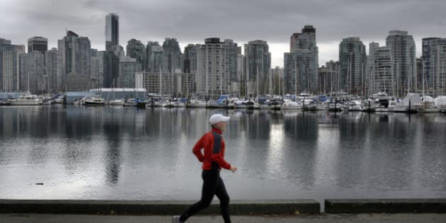 A jogger runs along the seawall in Vancouver's Stanley Park with Coal Harbor and the city in the backgound November 17, 2009. The city of Vancouver is gearing–up for the 2010 Winter Olympics with stores, restaurants and hotels getting ready to be in the world spotlight. Two–hours north of the city, Whistler is getting the olympic venues groomed and built for the alpine competitions  (Photo by Mark Boster/Los Angeles Times via Getty Images)