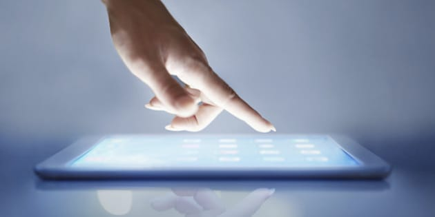 Cropped closeup of a woman's hand above a digital tablet