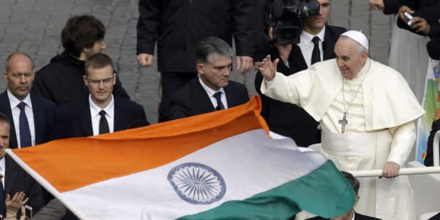 An Indian flag is waved near Pope Francis at the end of the Canonization mass for Eufrasia Eluvathingal, Amato Ronconi, Antonio Farina, Kuriakose Elias Chavara, Nicola Saggio da Longobardi and  Ludovico da Casoria, in St. Peter's Square, at the Vatican, Sunday, Nov. 23, 2014. Pope Francis has canonized six new saints, including a priest and a nun from the Indian state of Kerala, in a packed ceremony in St. Peter's Square. The Pope offered prayers Sunday for the saints, four Italians from disparate regions and two Indians from the Syro-Malabar Church, one of 22 Eastern rite churches that operates in full communion with Rome. Some 5,000 faithful traveled from Kerala state for the event, which was also streamed live onto screens set up outside churches in the southern region of India. (AP Photo/Gregorio Borgia)