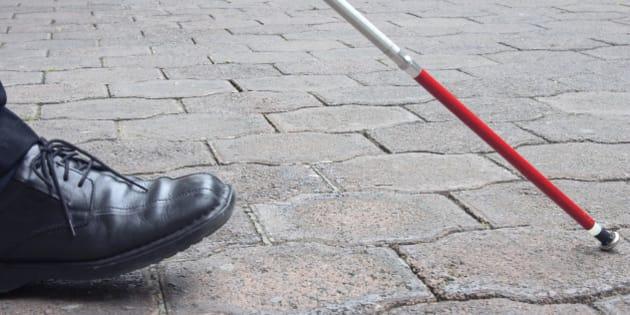 Close-Up of Blind Man's Black Shoe and White Cane Walking