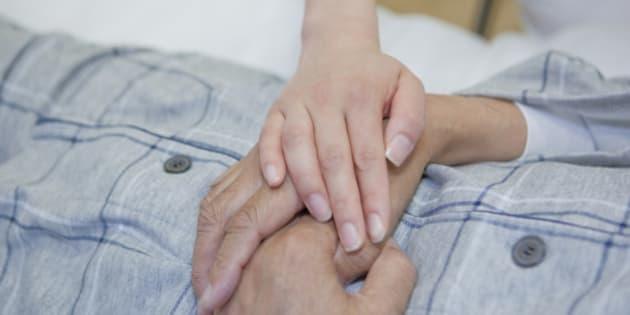 Nurse holding senior man's hand, Kanagawa Prefecture, Honshu, Japan