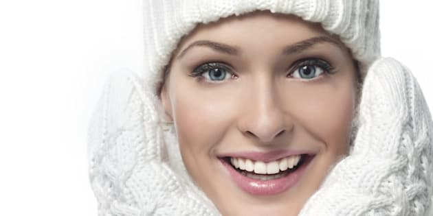 close-up portrait of beautiful young woman in warm clothing smiling looking at camera isolated on white teeth toothy smile skin care face
