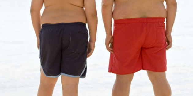 Overweight man and boy standing at beach