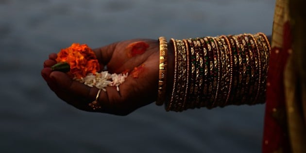A Nepalese Hindu woman holds offerings as she worships the sun in the Bagmati River in Kathmandu on November17, 2015, during the Chhath Festival which honours the sun god. People pay their respects to both the rising and setting sun during the Chhath festival when people express their thanks and seek blessings from the forces of nature. AFP PHOTO / Prakash MATHEMA        (Photo credit should read PRAKASH MATHEMA/AFP/Getty Images)