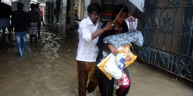 An Indian couple shelter under an umbrella as they walk with their child through floodwaters inundating Egmore Hospital in Chennai on December 1, 2015, during a downpour of heavy rain in the southern Indian city.  Heavy rains pounded several parts of the southern Indian state of Tamil Nadu and inundating most areas of Chennai, severely disrupting flights, train and bus services and forcing the postponment of half-yearly school exams.   AFP PHOTO/STR / AFP / STRDEL        (Photo credit should read STRDEL/AFP/Getty Images)