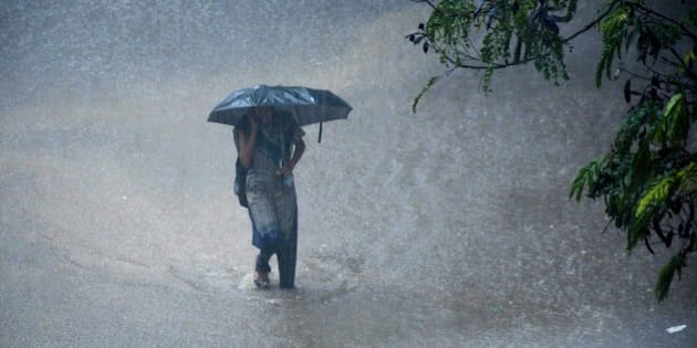 A young Indian woman walks under an umbrella through floodwaters in Chennai on December 1, 2015, during a downpour of heavy rain in the southern Indian city.  Heavy rains pounded several parts of the southern Indian state of Tamil Nadu and inundating most areas of Chennai, severely disrupting flights, train and bus services and forcing the postponment of half-yearly school exams.   AFP PHOTO/STR / AFP / STRDEL        (Photo credit should read STRDEL/AFP/Getty Images)