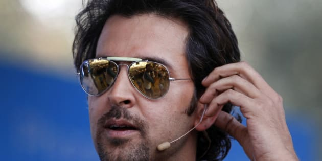 Bollywood actor Hrithik Roshan adjusts his microphone as he interacts with his fans during an event to promote his forthcoming science fiction movie 'Krrish 3' at a college campus in Bangalore, India, Monday, Oct. 7, 2013. Roshan on Monday launched a video game based on the movie in which he plays a superhero. (AP Photo/Aijaz Rahi)