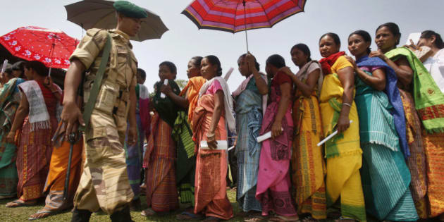 A security guard walks past Bodo tribal women standing in a queue to cast their votes, outside a polling center  in Jogeshpur village along the Indo-Bhutan border, about 120 kilometers (74 miles) west of Gauhati, India, Monday, April 11, 2011. Assam state votes Monday during the second and final phase of the state legislature elections in 64 of the 126 constituencies. (AP Photo/Anupam Nath)