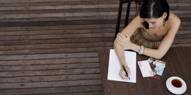 Woman writing postcards at table