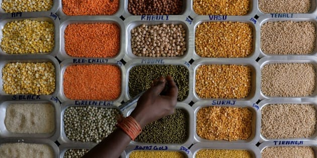 An Indian shopper examines pulses and food grains at a shop at the Agricultural Produce Marketting Committee (APMC) Yard in Bangalore on October 29, 2014.  AFP PHOTO/Manjunath KIRAN        (Photo credit should read MANJUNATH KIRAN/AFP/Getty Images)