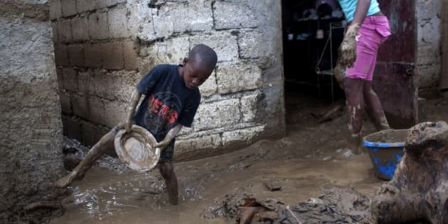 Winsky Pierre, left, 5, helps to drain mud from his flooded house after the passing of Tropical Storm Isaac in Port-au-Prince, Haiti, Sunday Aug. 26, 2012. The death toll in Haiti from Tropical Storm Isaac has climbed to seven after an initial report of four deaths, the Haitian government said Sunday. (AP Photo/Dieu Nalio Chery)