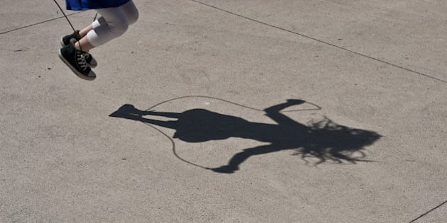 Strong shadow of a girl jumping rope