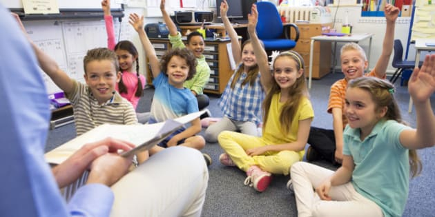 A group of children sit on the floor cross legged, listening to the teacher. They all have their hands raised in the air to answer a question.