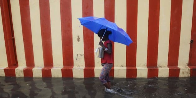 An Indian girl walks under an umbrella along a waterlogged street following heavy rain in Chennai on November 13, 2015. AFP PHOTO / STR        (Photo credit should read STRDEL/AFP/Getty Images)