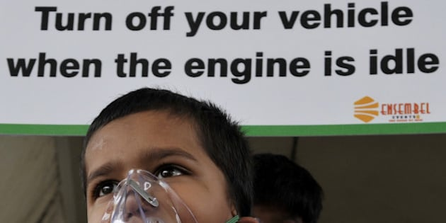 NEW DELHI, INDIA - JUNE 4: School children of Suraj Memorial High School wears an oxygen masks to raise awareness regarding the dangers of air pollution on the eve of World Environment Day at the IIT Red Light crossing on June 4, 2015 in New Delhi, India. The WHO study found New Delhi to have the dirtiest air, with an annual average of 153 micrograms of small particulates, known as PM2.5, per cubic metre.(Photo by Vipin Kumar/Hindustan Times via Getty Images)