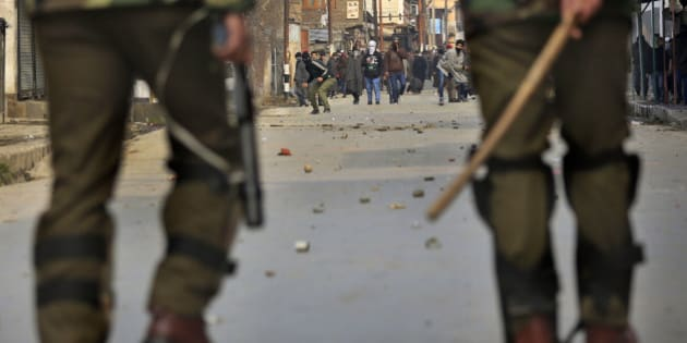 Masked Kashmiri protesters throw stones and bricks at Indian police during a strike in Srinagar, India, Friday, Jan. 31, 2014. Police in Indian Kashmir on Friday fired tear gas to disperse angry protesters who opposed the army's decision to close the Pathribal fake encounter case against five soldiers in connection with the killing of five innocent persons in March 2000 in Pathribal, a village that lies south of Kashmir. (AP Photo/Dar Yasin)