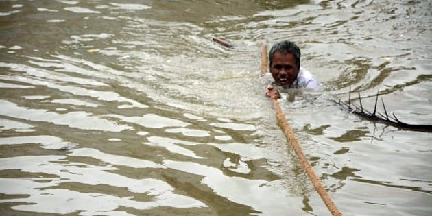 TOPSHOT - An Indian man clings to a rope as he makes his way through floodwaters in Chennai on December 2, 2015.   India has deployed troops to Tamil Nadu and closed the main airport there after heavy rains worsened weeks of flooding that has killed nearly 200 people in the southern coastal state. Thousands of rescuers carrying diving equipment, inflatable boats and medical equipment were battling to evacuate victims across the flooded state, officials said.    AFP PHOTO/STR / AFP / STRDEL        (Photo credit should read STRDEL/AFP/Getty Images)