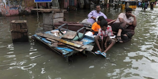 Indian residents sit on wooden pallets in floodwaters in Chennai on December 3, 2015. Thousands of rescuers raced to evacuate residents from deadly flooding, as India's Prime Minister Narendra Modi went to the southern state of Tamil Nadu to survey the devastation. More than 40,000 people have been rescued in recent days after record rains lashed the coastal state, worsening weeks of flooding that has killed 269 people. AFP PHOTO/STR / AFP / STRDEL        (Photo credit should read STRDEL/AFP/Getty Images)