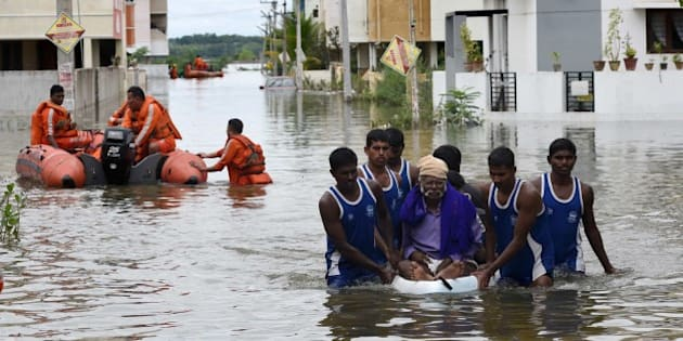 National Disaster Response Force (NDRF) rescue flood affected people during their relief operations in rain-hit areas on the outskirts of Chennai on November 17, 2015.   India has deployed the army and air force to rescue flood-hit residents in the southern state of Tamil Nadu, where at least 71 people have died in around a week of torrential rains.  AFP PHOTO        (Photo credit should read STR/AFP/Getty Images)