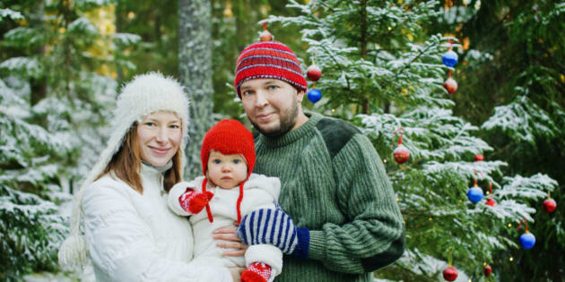 Finland, Heinola, Family with baby girl (12-17 months) near pine tree in forest