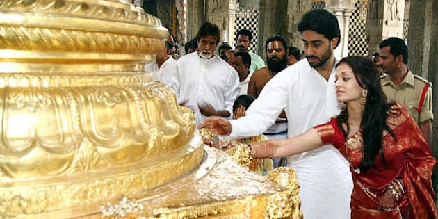 Tirupati, INDIA: Indian actors Abhishek Bachchan (2R) and Aishwarya Rai (R) are watched by Amitabh Bachchan (C) as they touch a golden statue during a visit to The Lord Venkatesh Wara Temple at Tirupati,some 550 kms south of Hyderabad,22 April 2007.  Bollywood stars Aishwarya Rai and Abhishek Bachchan began life as 'Mr and Mrs Bachchan' 21 April, after three days of wedding celebrations for Indian cinema's ultimate power couple.  AFP PHOTO/NOAH SEELAM (Photo credit should read NOAH SEELAM/AFP/Getty Images)
