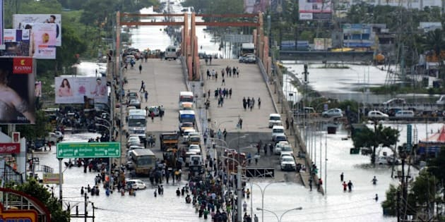 Indian residents and motorists gather on a flyover as others wade through floodwaters in Chennai on December 3, 2015.  Thousands of rescuers raced to evacuate residents from deadly flooding, as India's Prime Minister Narendra Modi went to the southern state of Tamil Nadu to survey the devastation. More than 40,000 people have been rescued in recent days after record rains lashed the coastal state, worsening weeks of flooding that has killed 269 people AFP PHOTO/STR / AFP / STRDEL        (Photo credit should read STRDEL/AFP/Getty Images)