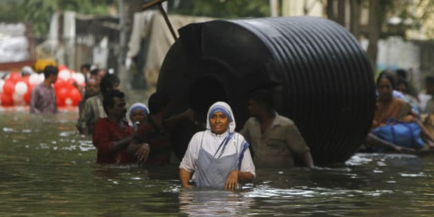 People use a water tank for floatation as they wade through flood waters in Chennai, India, Thursday, Dec. 3, 2015. The heaviest rainfall in more than 100 years has devastated swathes of the southern Indian state of Tamil Nadu, with thousands forced to leave their submerged homes and schools, offices and a regional airport shut for a second day Thursday.( AP Photo)