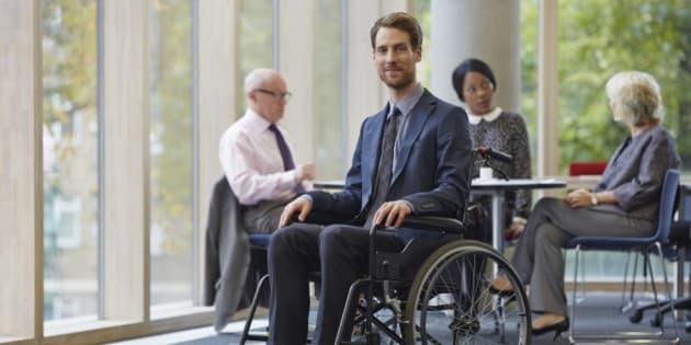Businessman in wheelchair, meeting in background