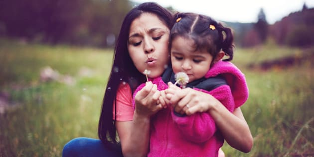Mother and daughter blowing dandelion seeds.