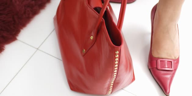 Feet of woman in red high heels with red purse