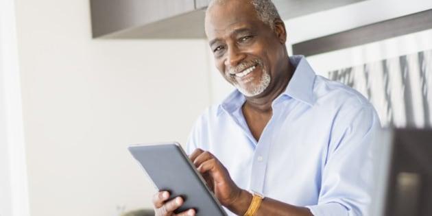 USA, New Jersey, Jersey City, Portrait of senior man using digital tablet in office
