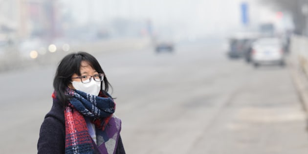 BEIJING, CHINA - DECEMBER 07:  (CHINA OUT) A woman wearing mask walks along a road in heavy smog on December 7, 2015 in Beijing, China. China's National Meteorological Center (NMC) issued a yellow alert on Sunday as heavy smog will cover the country's northern regions in the following two days.  (Photo by ChinaFotoPress/ChinaFotoPress via Getty Images)