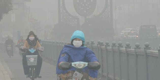 SUZHOU, CHINA - DECEMBER 07:  (CHINA OUT) Cyclists wearing masks ride along a road in heavy smog on December 7, 2015 in Suzhou, China. China's National Meteorological Center (NMC) issued a yellow alert on Sunday as heavy smog will cover the country's northern regions in the following two days.  (Photo by ChinaFotoPress/ChinaFotoPress via Getty Images)